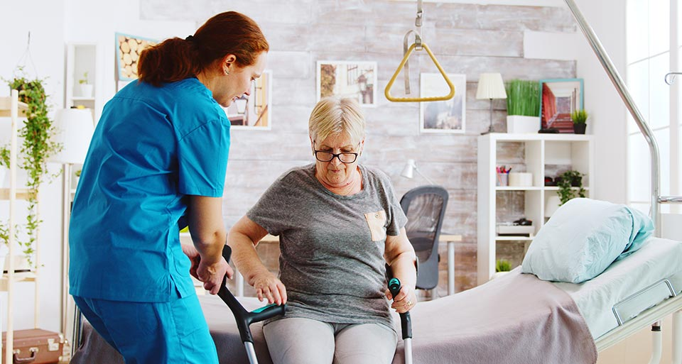 Pride in supporting our staff: A nurse assisting her patient to stand with crutches at her bedside.